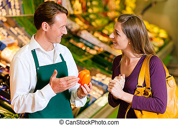 Woman in supermarket and shop assistant - woman in a ...