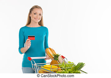 Woman in supermarket. Cheerful young woman standing near shopping cart and holding credit card while isolated on white