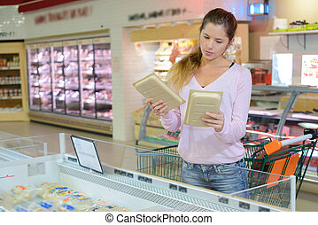 Woman in supermarket comparing two packs of food