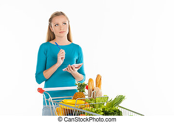 Woman in supermarket. Thoughtful young woman standing near shopping cart and holding note pad while isolated on white
