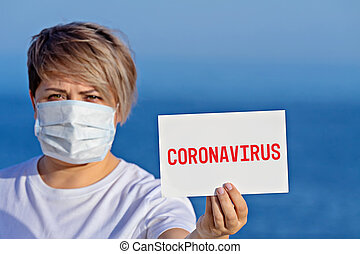 Woman in surgical mask holds blank with text coronavirus 2019