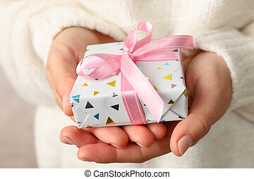 Woman in sweater holding gift box with pink bow, close up