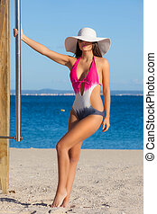 woman in swimsuit on beach vacation or summer holiday