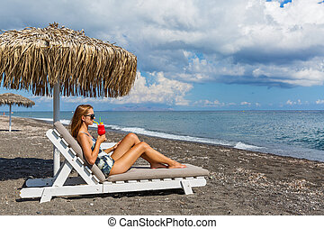 Woman in swimsuit on the beach with a cocktail
