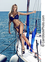 Woman in swimsuit posing on yacht