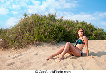 Woman in swimsuit sitting on the sand