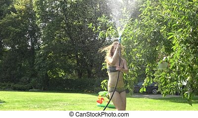 woman in swimsuit watering with water hose in the garden.