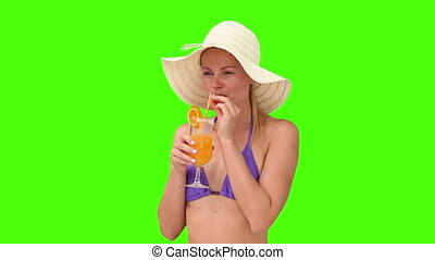 Woman in swimsuit with an hat sipping a cocktail
