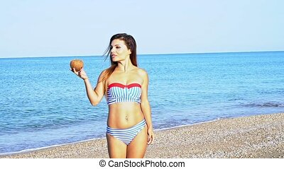 Woman in swimsuit with cocktail on the beach