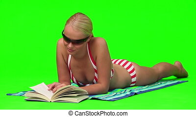 Woman in swimsuit with sunglasses reading a book