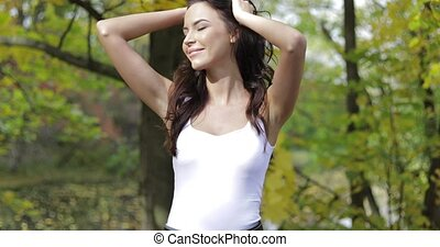 Woman in tank top smoothing hair - Beautiful woman in white...