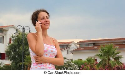 Woman in tank top speaking by mobile phone - woman in tank...