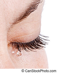 Sad woman concept - closed eyelid closeup with a teardrop on eyelashes - isolated