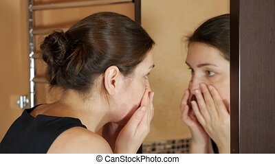 Woman in the bath crushes pimples in front of the mirror.
