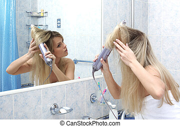 Woman in the bathroom at mirror drying hair