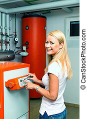 Woman in the boiler room for heating. - A young woman in the...