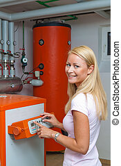 Woman in the boiler room for heating. Save energy - A young...