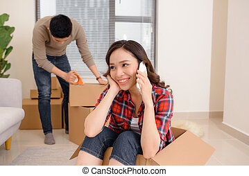 woman in the box, housewarming, the man is sitting on the couch, a new apartment
