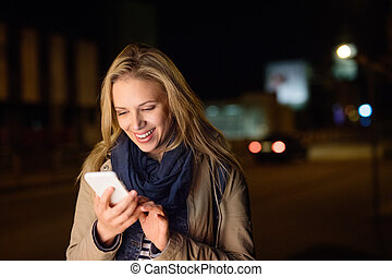 Woman in the city at night holding smartphone, texting.