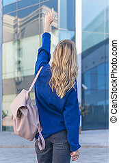 Woman in the city points hand up