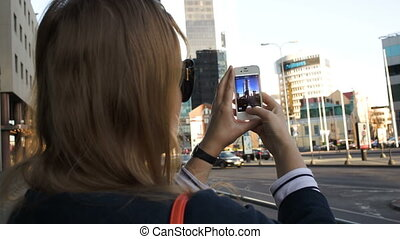 Woman in the city taking pictures with her smartphone