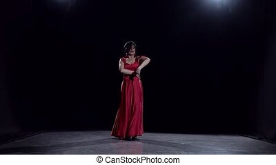Woman in the dark room performs elegant movements dance....