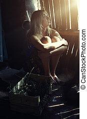 Woman in the dark rural barn