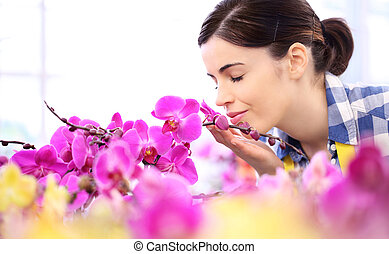 woman in the garden of flowers, touches and smells an orchid