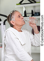 Woman in the gym drinking water