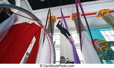 Woman in the gym performs a gymnastic elements in the air on...