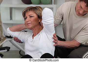 Woman in the gym with personal trainer