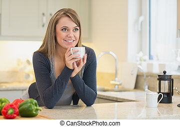 Woman in the kitchen drinking hot b