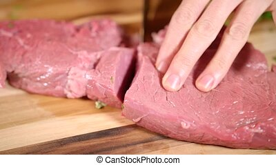 Woman in the kitchen is cutting meat.