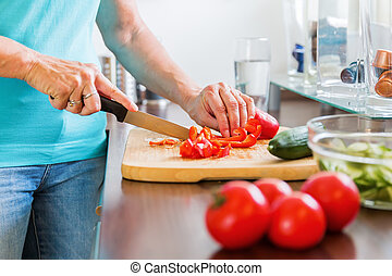woman in the kitchen preparing salad