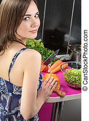 Woman in the kitchen preparing salad