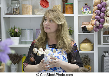 Woman in the kitchen with garlic