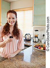Woman in the kitchen with her cellphone