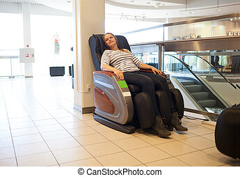 Woman in the massage chair in the trade centre