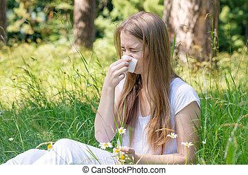 Woman in the meadow sneezes