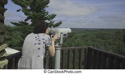 Woman in the mountains looks through telescope
