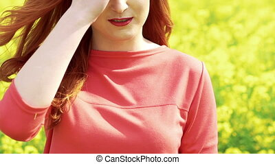 Woman in the rape-field touching her hair, smiling. Slow motion