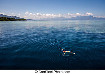 Woman relaxing and swimming in a tropical sea