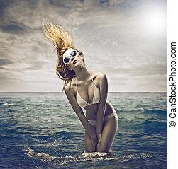woman in the sea - young woman with bikini and sunglasses in...