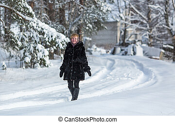 Woman in the snowy russian village at winter.