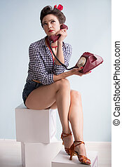 Woman in the style of the fifties. Beautiful retro girl with a retro phone in the studio.