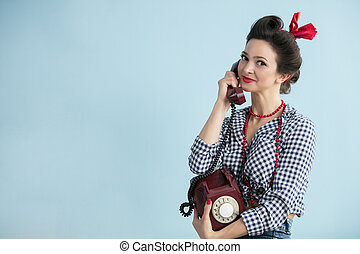Woman in the style of the fifties. Beautiful retro woman with a dial phone.
