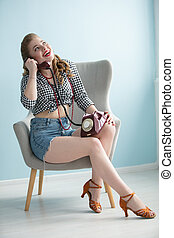 Woman in the style of the fifties. Beautiful retro woman with a phone in an armchair.