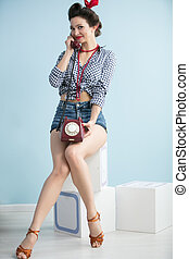 Woman in the style of the fifties. Beautiful retro woman with a phone on a blue background.