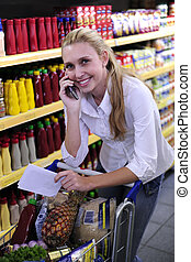 Woman in the supermarket talking on phone with shopping list