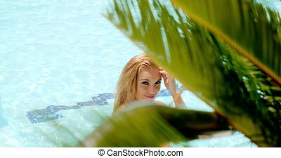 Woman in the Swimming Pool Behind Palm Leaves